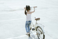 Full length of girl with bicycle walking on road during summer - CAVF55810