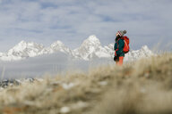 Side view of female hiker with backpack standing against snowcapped mountains and cloudy sky - CAVF55828