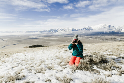 Female hiker photographing with camera while kneeling on snowy field against mountains - CAVF55831
