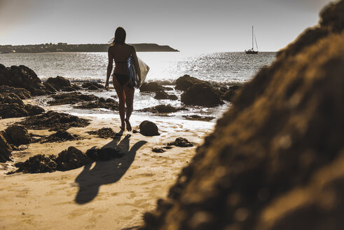 France, Brittany, young woman carrying surfboard on a rocky beach at the sea - UUF15884