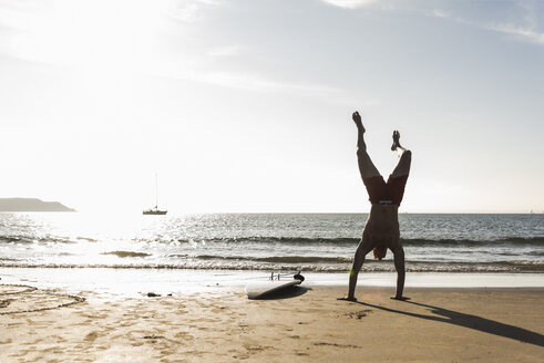 France, Brittany, young man doing a handstand on the beach next to surfboard - UUF15914