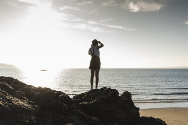France, Brittany, rear view of young woman standing on rock at the beach at sunset - UUF15929
