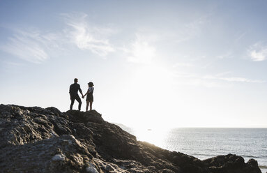 France, Brittany, rear view of young couple standing hand in hand on rock at the beach at sunset - UUF15932