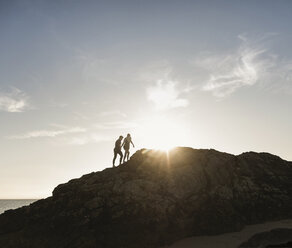 France, Brittany, young couple climbing on a rock at the beach at sunset - UUF15935