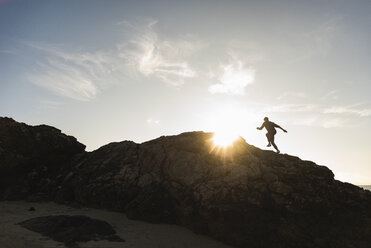 France, Brittany, young man running on a rock at sunset - UUF15938