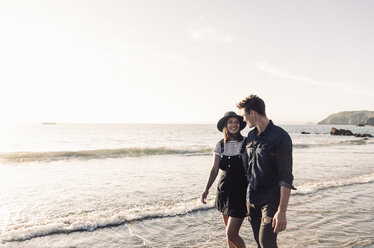 France, Brittany, happy young couple walking at the beach - UUF15941
