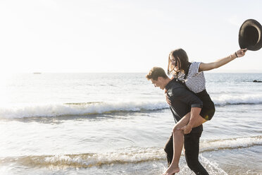 France, Brittany, happy young man carrying girlfriend piggyback at the beach - UUF15944