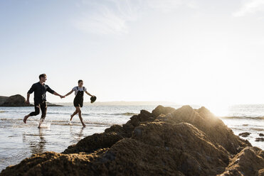 France, Brittany, happy young couple running hand in hand on the beach - UUF15947