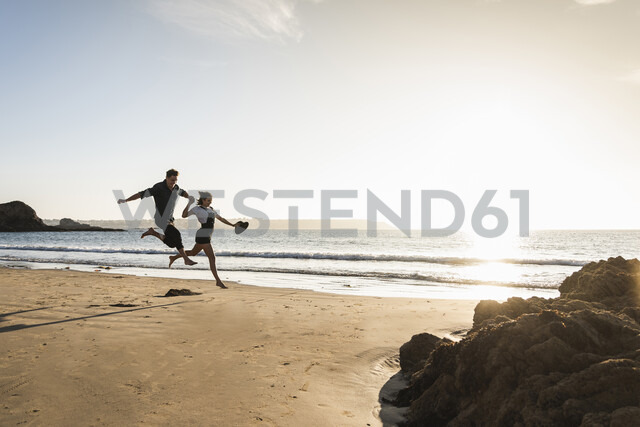 France, Brittany, happy young couple jumping on the beach at sunset - UUF15950 - Uwe Umstätter/Westend61
