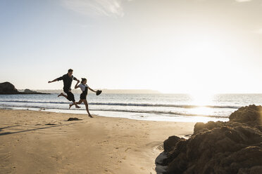 France, Brittany, happy young couple jumping on the beach at sunset - UUF15950