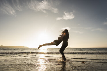 France, Brittany, happy young couple hugging on the beach at sunset - UUF15953