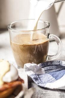 Pouring milk into a mug of coffee - SBDF03825