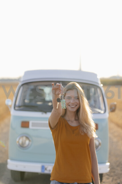 Happy young woman holding car key at camper van in rural landscape - GUSF01387 - Gustafsson/Westend61