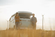 Happy couple at camper van in rural landscape with wind turbines in background - GUSF01393