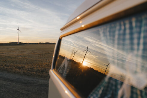 Camper van in rural landscape with wind turbines at sunset - GUSF01399