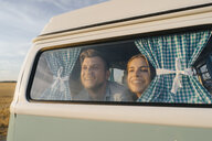 Happy young couple leaning against window of a camper van - GUSF01411