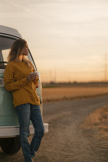Young woman standing at camper van in rural landscape at sunset - GUSF01414