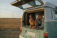 Couple brushing teeth in camper van in rural landscape - GUSF01417