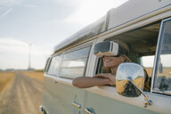 Smiling woman wearing VR glasses leaning out of window of a camper van - GUSF01420