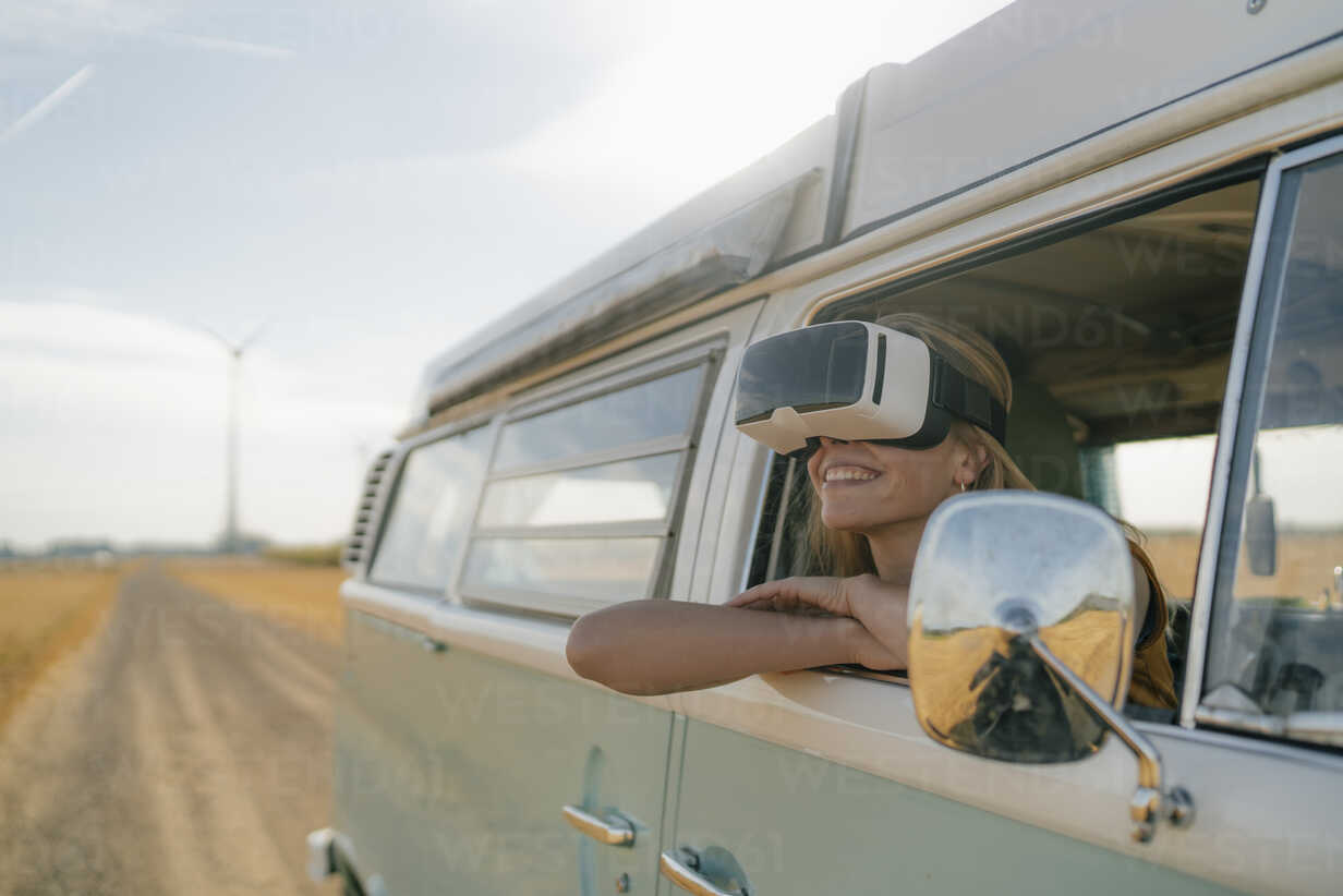 Smiling woman wearing VR glasses leaning out of window of a camper van - GUSF01420 - Gustafsson/Westend61