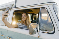 Smiling woman taking a selfie in a camper van with man driving - GUSF01426