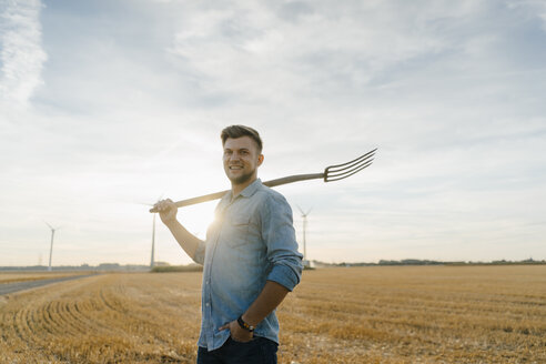 Portrait of smiling young man holding pitchfork standing on stubble field - GUSF01429