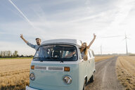 Happy couple leaning out of window of a camper van in rural landscape - GUSF01435
