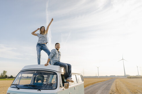Happy couple on roof of a camper van in rural landscape - GUSF01438