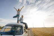 Young couple on roof of a camper van in rural landscape - GUSF01441