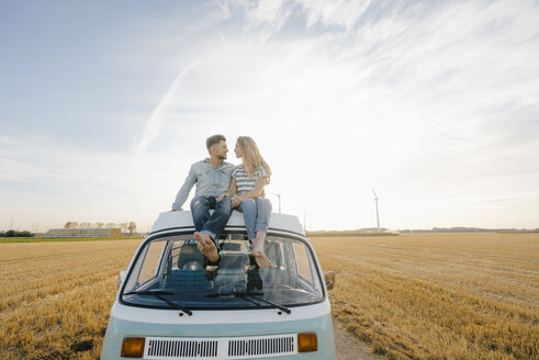 Smiling young couple on roof of a camper van in rural landscape - GUSF01444