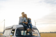Smiling young couple on roof of a camper van in rural landscape - GUSF01447