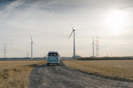 Camper van in rural landscape with wind turbines at sunset - GUSF01450