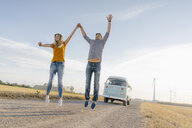 Exuberant couple jumping on dirt track at camper van in rural landscape - GUSF01453