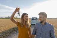 Young couple with car key on dirt track at camper van in rural landscape - GUSF01456