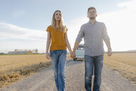 Young couple walking on dirt track at camper van in rural landscape - GUSF01459