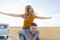 Playful young couple at camper van in rural landscape - GUSF01468