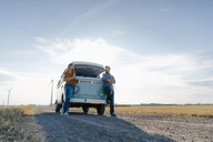 Happy couple standing at camper van in rural landscape - GUSF01471