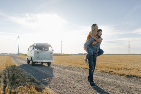 Young man carrying girlfriend piggyback on dirt track at camper van in rural landscape - GUSF01474