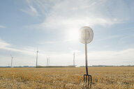 Pitchfork in field in rural landscape with wind turbines in background - GUSF01480
