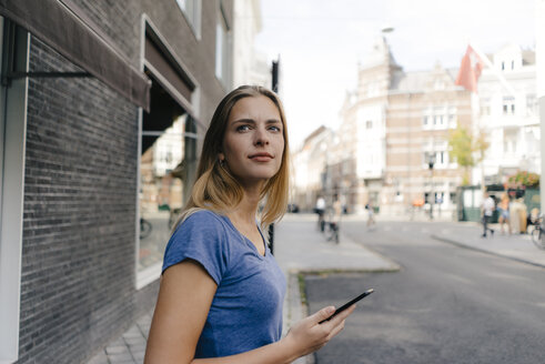 Netherlands, Maastricht, smiling young woman with cell phone in the city looking around - GUSF01504