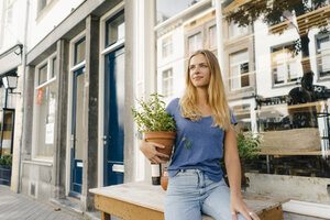 Netherlands, Maastricht, blond young woman holding flowerpot in the city - GUSF01516