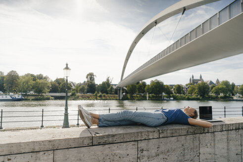 Netherlands, Maastricht, young woman lying on a wall at the riverside - GUSF01528