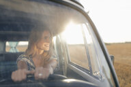 Happy young woman driving camper van in rural landscape - GUSF01546