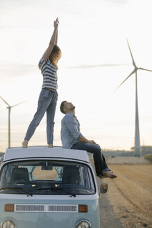 Happy couple on roof of a camper van in rural landscape - GUSF01549