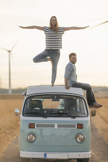 Young couple on roof of a camper van in rural landscape - GUSF01552