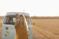 Happy young woman holding car key at camper van in rural landscape - GUSF01555