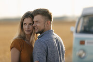 Affectionate young couple at camper van in rural landscape - GUSF01558