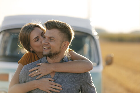 Happy affectionate young couple at camper van in rural landscape - GUSF01561