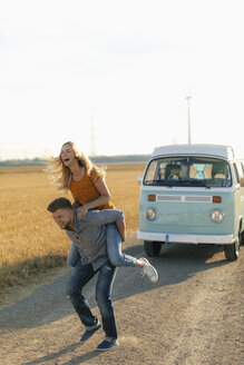Playful young couple at camper van in rural landscape - GUSF01564