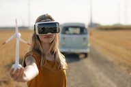 Young woman with VR glasses at camper van in rural landscape holding wind turbine model - GUSF01567